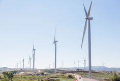 White wind turbines generating electricity in wind power station. With strawberries tree growing plantation royalty free stock photography