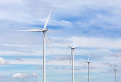 White wind turbines generating electricity in wind power station alternative renewable energy from nature Stock Image