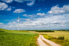 White wind turbines on green field as alternative energy. Poland, Europe Stock Images