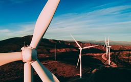White Wind Turbines or Modern Windmills in the mountains landscape. On the sunset and blue sky on the background stock images
