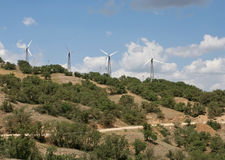 The white wind turbines on the mountain with treed slopes and the earth road. Royalty Free Stock Image