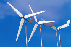 White wind turbines producing alternative energy on blue sky Stock Photo