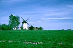 White windmill on green farm field Royalty Free Stock Photo