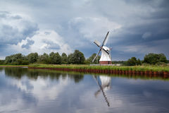 White windmill over clouded sky Stock Photos