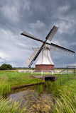 White windmill by river over clouded sky Stock Image
