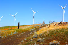White Windmills. On colorful hillside in eastern Oregon generating renewable energy electricity, with driveway down hillside. Clear blue sky Stock Photo