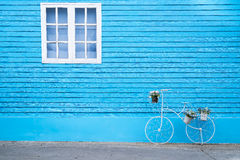White window on the blue wall with bike shaped flowers pot. Stock Image