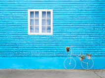 White window on the blue wall with bike shaped flowers pot. Royalty Free Stock Image