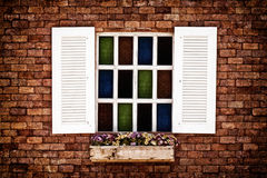 White window brick wall. White window colorful glass on brick wall  of vintage house style Royalty Free Stock Photography