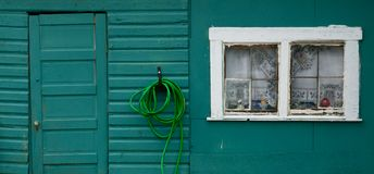 White Window - Green Hose II. Closeup of a green wall with a door, a hose and a white window vector illustration