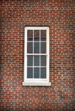 White Window Isolated by Red Brick. Red brick isolating a white window with horizontal reflections, historic SoHo New York Stock Image