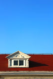 The white window of the loft on the red roof Stock Photos