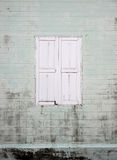 White window on old wall with house. Royalty Free Stock Image