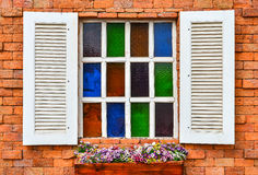 White window on red brick wall. And flower in wooden vase Royalty Free Stock Photos