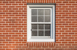 White  window on a red brick wall, sun reflction on the glass Royalty Free Stock Image