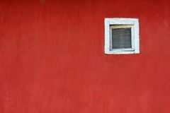 White window on red wall. A white window on a red wall on the street royalty free stock image