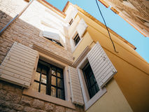 White window shutters. The facade of houses. In Montenegro Royalty Free Stock Photo