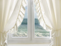 White window with view to the sea. Travel / summer holiday concept - window with white curtains, overviewing the sea Royalty Free Stock Photography