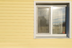 White window on the wall lined with yellow siding Stock Photo