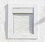White window with white blinds on a white wall. A white window with white blinds on a white wall Royalty Free Stock Photos