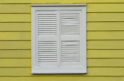White window on yellow wall. White shuttered window on yellow wall Stock Images