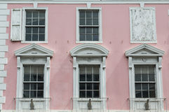 White Windows on Old Pink Government Building in Bahamas Stock Photo