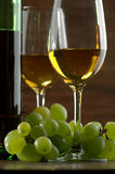 White wine. Bottles and glasses of excellent wine on a dark background Stock Photos