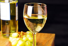 White wine. With grapes ,bottle and black background Royalty Free Stock Photo
