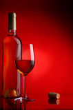 White wine. The big glass of white wine and bottle on a red background Stock Images