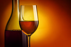 White wine. Bottle and glass of wine on a yellow background Stock Photo