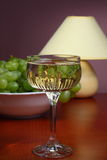 White wine. Glass of white wine on wooden table with bowl of grapes and table lamp Royalty Free Stock Images