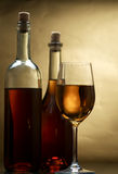 White wine. Bottle and glass of wine on a dark background Stock Photos