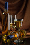 White wine. Bottles and glasses of excellent wine on a dark background Stock Image