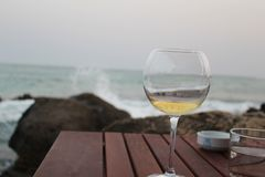 White wine against the Mediterranean at Sunset. Dinner in Kelibia on Tunisia`s Cap Bon. The sea, the sky, the waves, so fresh and unique and at a fraction of the royalty free stock images
