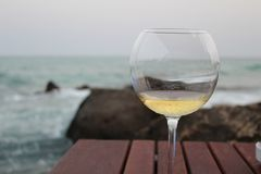 White wine against the Mediterranean at Sunset. Dinner in Kelibia on Tunisia`s Cap Bon. The sea, the sky, the waves, so fresh and unique and at a fraction of the stock photo