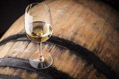 White wine on a barrel. Glass of white wine standing on an oak barrel in a cellar royalty free stock photography