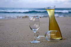 White wine on beach. White wine in carafe and glasses on beach royalty free stock images