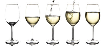 White wine being poured into an empty wine glass. A compite image of white wine being poured into an empty wine glass  on white Royalty Free Stock Photography