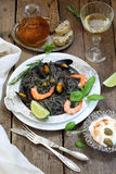 White wine and black spaghetti with mussels, shrimp and tomatoes. Black spaghetti with mussels, shrimp, garlic, tomato and white wine Stock Images