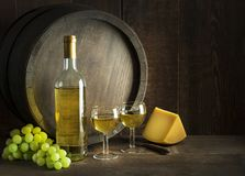 White wine bottle and glass with barrel background. Bottle of white wine with cheese food on old board and barrel. Wine bottle mockup stock photos