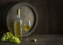 White wine bottle and glass with barrel background. Bottle of white wine with cork. Glass of wine with barrel background stock photos