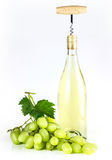 White wine bottle, corkscrew, and grapes. Royalty Free Stock Image