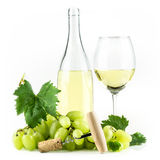 White wine bottle, corkscrew, wineglass, and grapes. Stock Photos