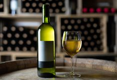 White wine bottle with a filled wineglass on a barrel in a cellar. Switzerland royalty free stock photo