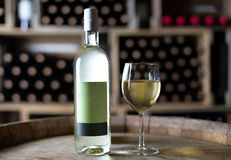 White wine bottle with a filled wineglass on a barrel in a cellar. Switzerland royalty free stock images