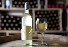 White wine bottle with a filled wineglass on a barrel in a cellar. Switzerland stock photography