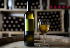 White wine bottle with a filled wineglass on a barrel in a cellar. Switzerland stock image