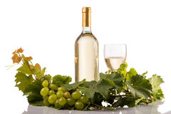 White wine bottle and glass on white background with vine leaves and grapes. Studio shot of white wine bottle and glass isolated on white background with vine Royalty Free Stock Image