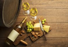 White wine bottle and glass with barrel background. Bottle of white wine with snack food on old board and barrel. Wine bottle mockup stock image