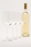 White wine bottle with wineglasses lined up. Isolated white wine bottle with wineglasses lined up stock images